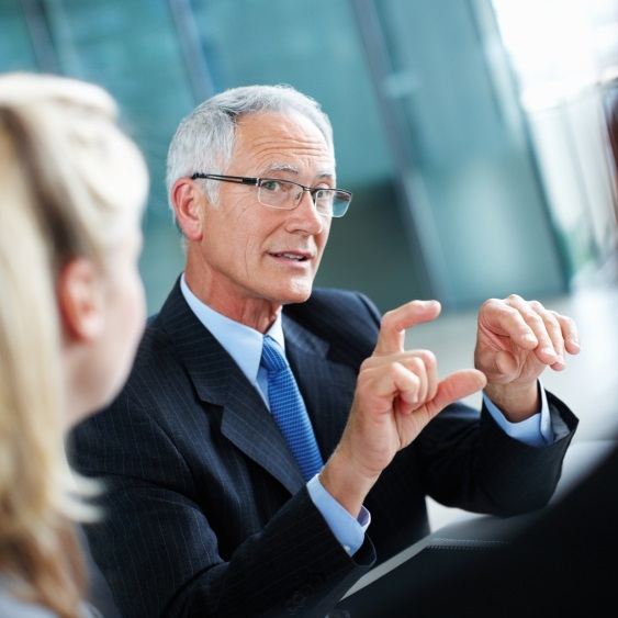 Portrait of smart manager discussing with associates in meeting