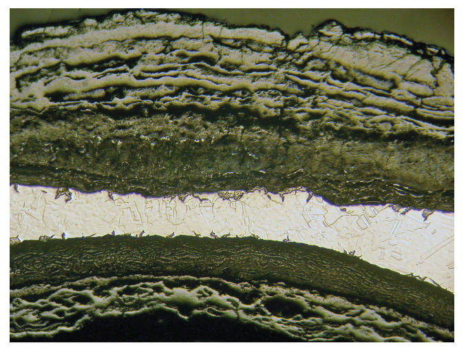 Optical micrograph of corroded steel pipe showing intergranular attack and reduced thickness 16X.